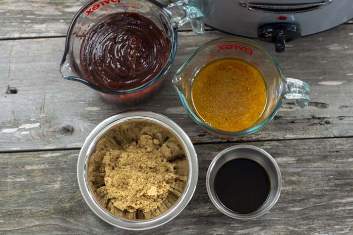 Glass measuring cups with bbq sauce and zesty Italian dressing next to stainless steel bowls of brown sugar and Worcestershire sauce with the slow cooker behind all on a wooden surface