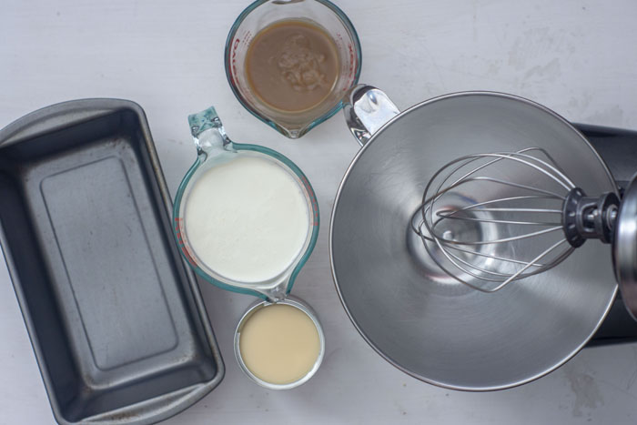 Ingredients for butterbeer ice cream: an empty loaf pan and empty stand mixer with glass measuring cups of butterscotch syrup and heavy cream with a can of sweetened condensed milk in between on a white surface