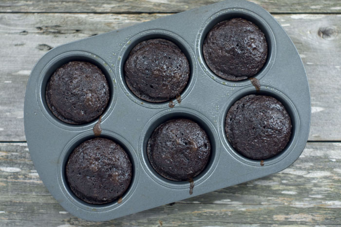 Six chocolate cupcakes in a metal cupcake pan on a wooden surface