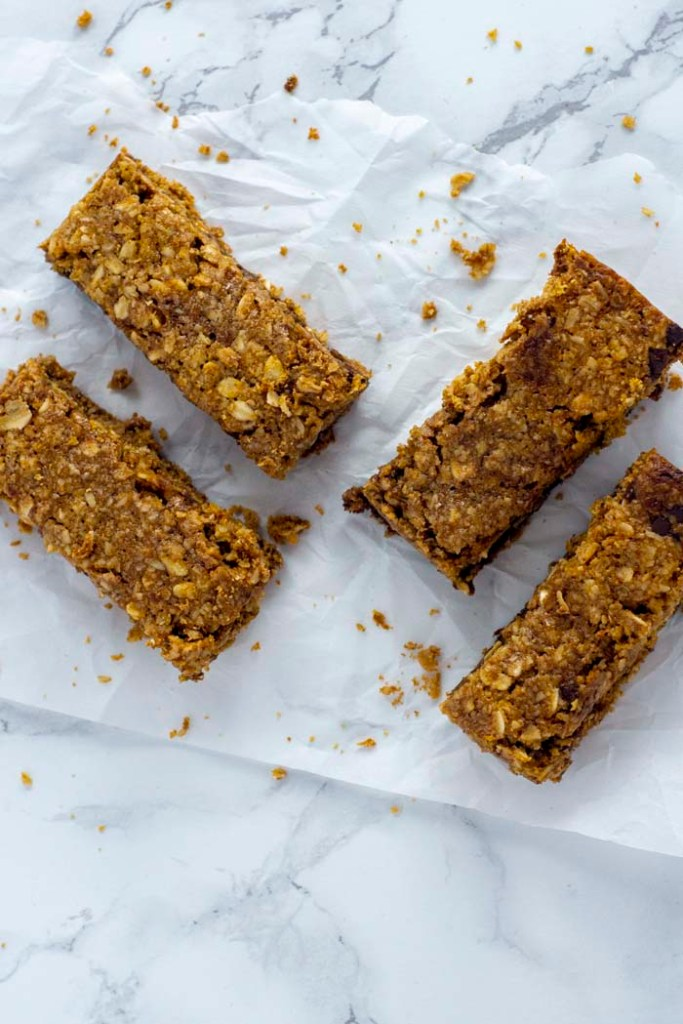 Four granola bars on a piece of wax paper on a white and grey marble surface (vertical)