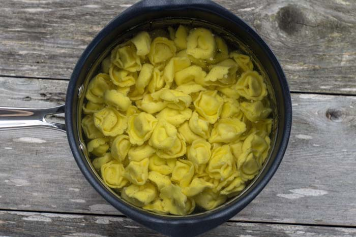 Tortellini cooking in a saucepan on a wooden surface