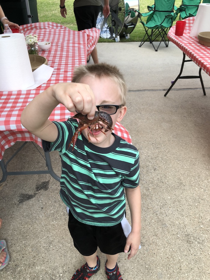 Tyler holding a crawfish at our neighbor's crawfish boil in 2018.
