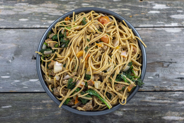 Spaghetti noodles mixed with sausage, spinach, onions, and tomato in a round metal baking pan on a wooden surface