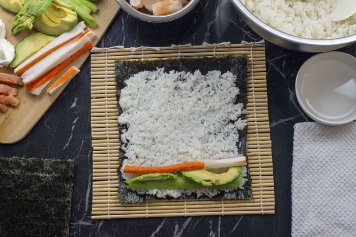 Sushi setup with sliced ingredients on a bamboo cutting board next to a white bowl of shrimp and another bowl of sushi rice with a bowl of water and a white towel and a pile of seaweed surrounding a bamboo mat with seaweed topped with sushi rice and slices of crab, cucumber, and avocado all on a black and white marble surface