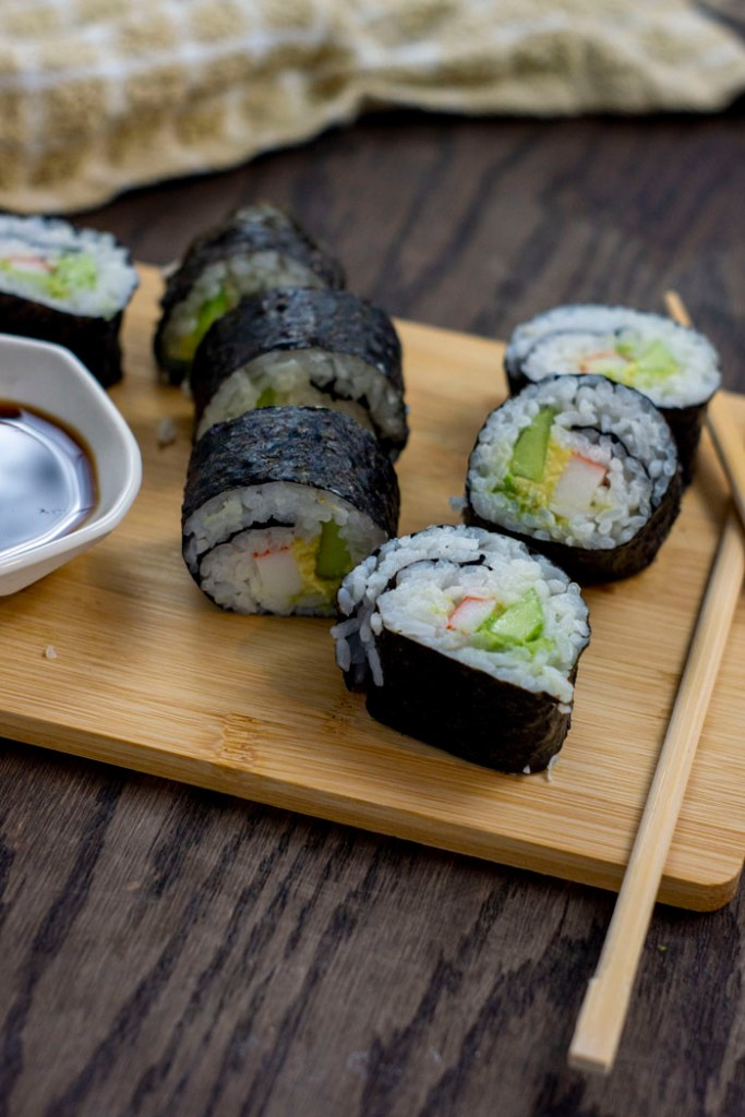 California Roll next to bamboo chopsticks and a white bowl of soy sauce on a bamboo cutting board with a tan and white towel behind all on a wooden surface (vertical)