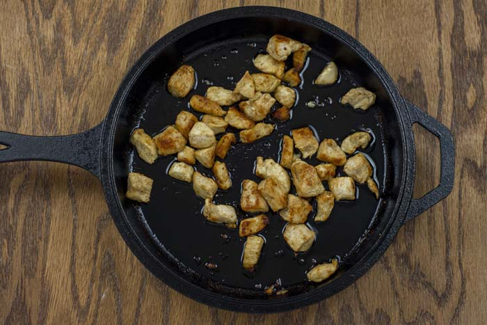 Diced cooked chicken in a cast iron skillet on a wooden surface
