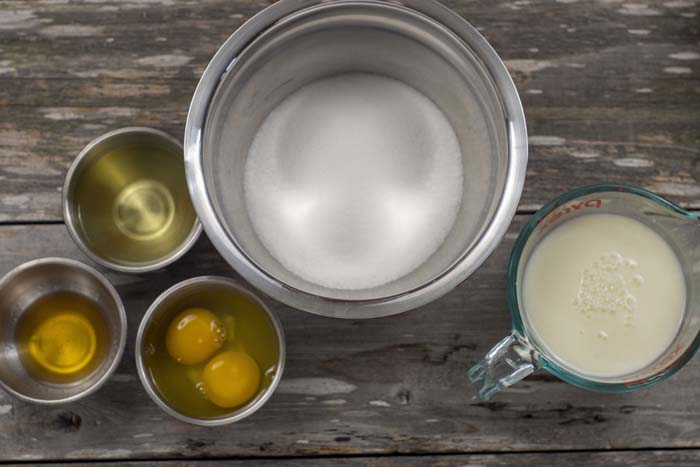 Stainless steel bowls with oil, sugar, vanilla extract, and eggs next to a glass measuring cup of buttermilk on a wooden surface