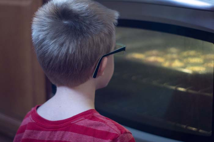 Young boy watching muffins bake in the oven