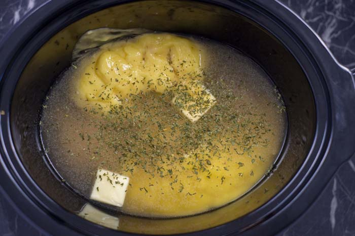 Raw chicken topped with butter with chicken soup and chicken broth sprinkled with seasonings in a black slow cooker on a black and white marble surface