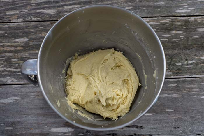 Dry cake batter in a stainless steel bowl on a wooden surface