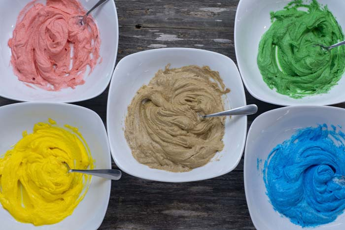 Five white bowls with buttercream frosting and a spoon in each. Frosting is colored with red, blue, yellow, green, and brown coloring