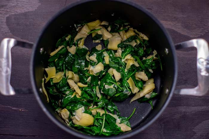 Chopped artichoke hearts with wilted spinach leaves in oil in a large stockpot on a wooden surface