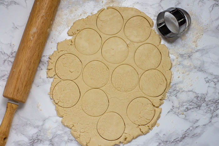 Dough rolled out with circles cut into it next to a round biscuit butter and a wooden rolling pin on a white and grey marble surface