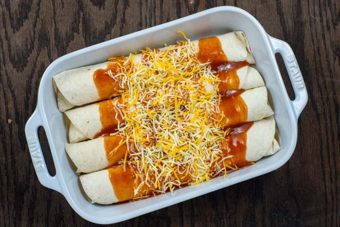4 chicken enchiladas rolled up and drizzled with enchilada sauce and topped with shredded cheese in a white casserole dish on a wooden surface