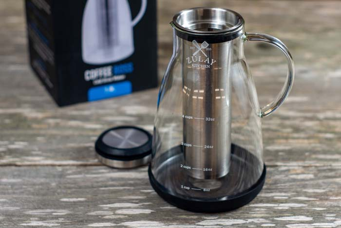 Empty glass cold brew coffee maker next to the lid with the box behind all on a wooden surface