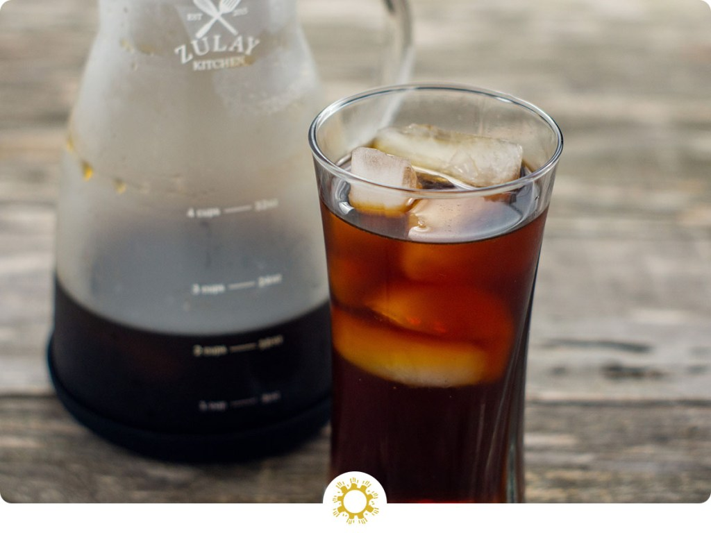 Cold brew coffee with cubes of ice in a glass cup with a carafe of cold brew coffee behind on a wooden surface (with logo overlay)