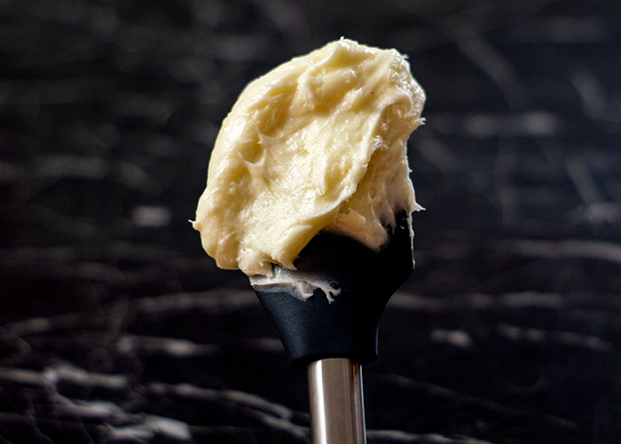 Large scoop of cream cheese frosting on a black rubber spatula with a metal handle over a black and white marble surface