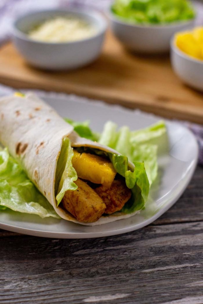 Hawaiian chicken wraps filled with bbq chicken, pineapple chunks, and lettuce in a flour tortilla over a bed of lettuce on a square white plate with a bamboo platter behind with round white bowls of cheese, lettuce, and pineapple all on a wooden surface (vertical)