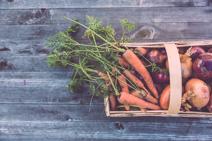 Wooden basket filled with vegetables on a wooden surface for 30 day no waste challenge