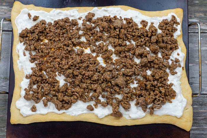 Baked pizza crust with cream cheese and sour cream mixture spread to the edges topped with prepared taco meat sitting on a baking stone on a wooden surface