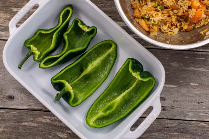 Two poblano peppers halved and seeded laying in a white casserole dish next to a stainless steel bowl of mixed filling all on a wooden surface