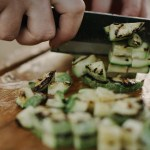 Woman's hand using a chef's knife to chop a green vegetable on a bamboo cutting board (with simple title overlay)
