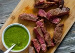 Slices of brown sugar steak next to a white bowl of green chimichurri sauce on a bamboo cutting board on a wooden surface