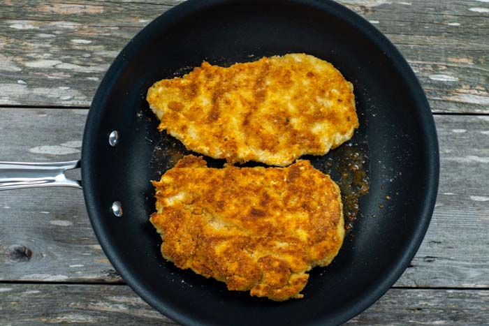 Cooked breaded chicken in a skillet on a wooden surface