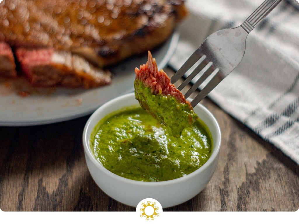 Piece of cooked steak on a stainless steel fork being dipped into a round white bowl of green chimichurri sauce with a plate of grilled steak in the back next to a white and grey towel all on a wooden surface (with logo overlay)