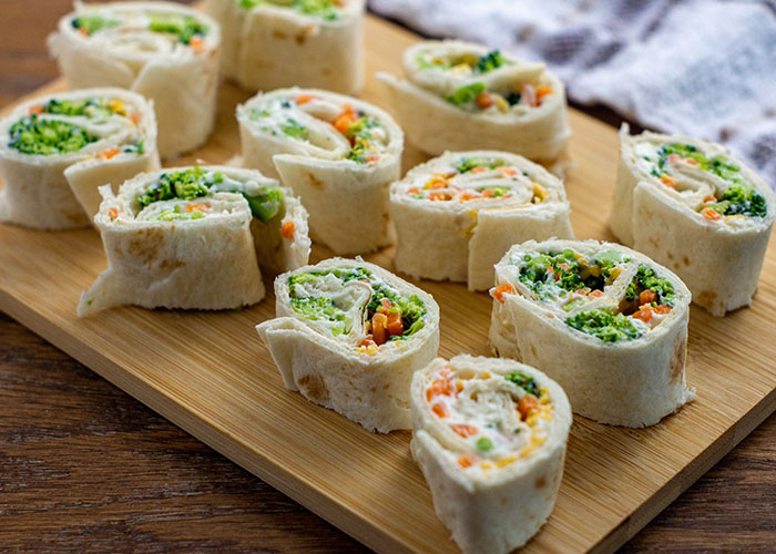 Veggie tortilla pinwheels on a bamboo tray with a white and brown towel behind all on a wooden surface