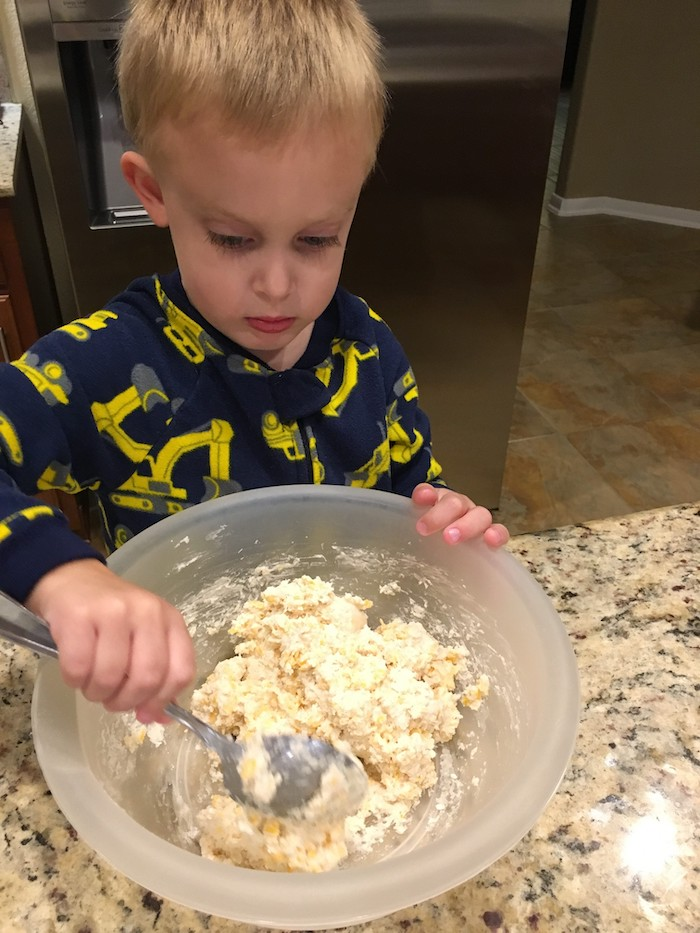 Young boy in pajamas mixing cheddar biscuit dough in a semi-transparent plastic bowl at a granite countertop