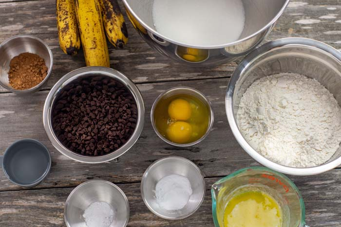 Ingredients in stainless steel bowls for chocolate chip banana bread on a wooden surface