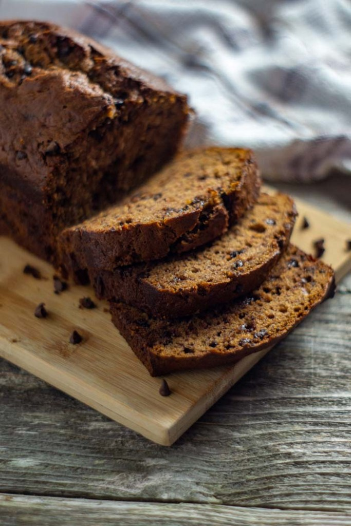 Loaf of chocolate chip banana bread with a few slices cut off on a bamboo tray with a white and brown towel behind all on a wooden surface (vertical)