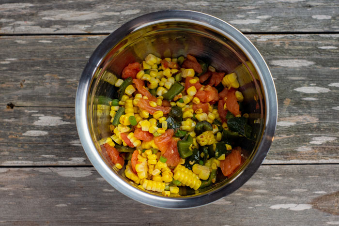 Corn, peppers, tomatoes, and green onion in dressing in a stainless steel mixing bowl on a wooden surface