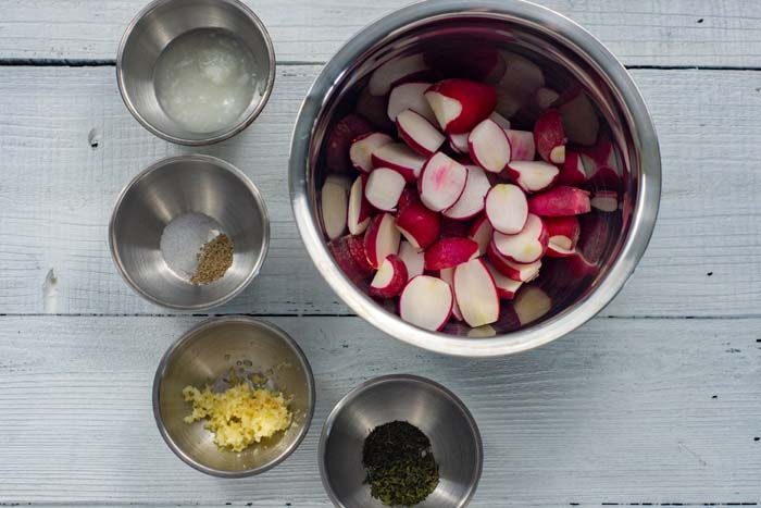 Ingredients for Garlic-Roasted Radishes in stainless steel bowls: trimmed radishes, coconut oil, salt and pepper, minced garlic, and parsley all on a white wooden surface