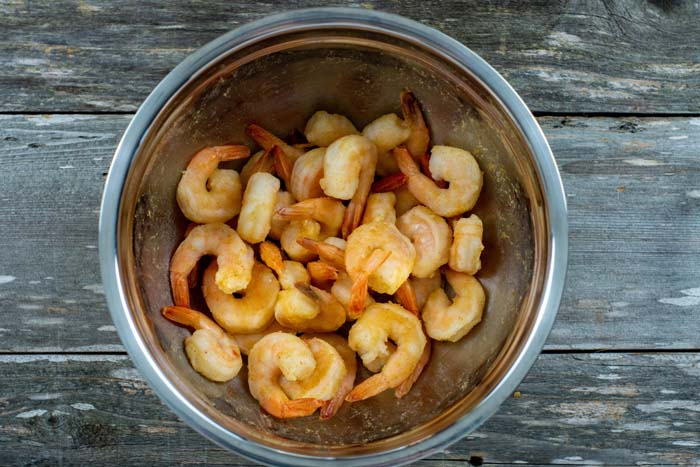 Shrimp marinating in lime juice in a stainless steel bowl on a wooden surface