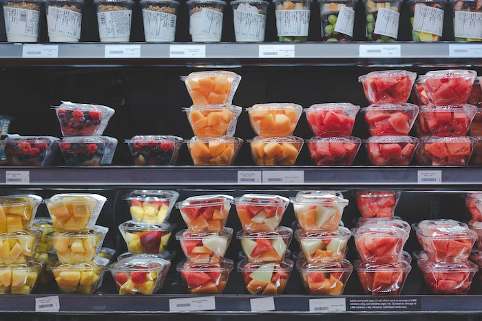 Cut fruit in plastic containers on refrigerated shelves