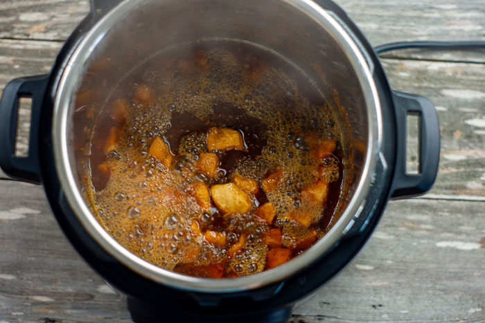 Chicken and sauce bubbling in an instant pot with steam coming out on a wooden surface