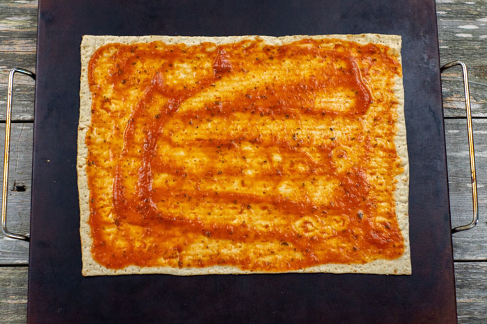 Flatbread covered with pizza sauce on a baking stone on a wooden surface