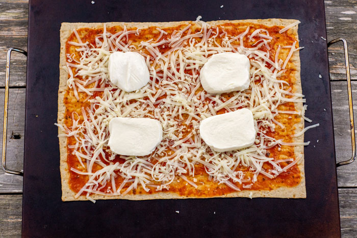Flatbread covered with pizza sauce, shredded mozzarella cheese, and fresh mozzarella cheese on a baking stone on a wooden surface
