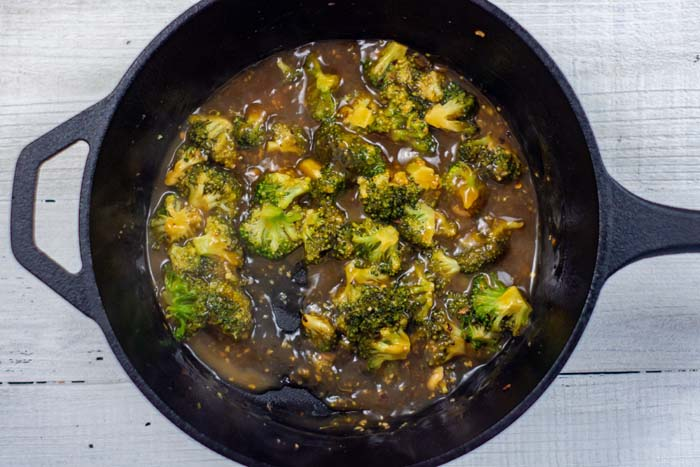 Broccoli in sweet and sour sauce in a cast-iron skillet on a white wooden surface
