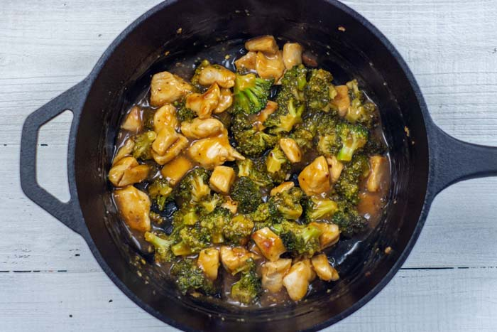Sweet and sour chicken with broccoli in sauce in a cast-iron skillet on a white wooden surface