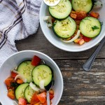 Two white bowls of cucumber summer salad with stainless steel spoons next to a white and brown towel all on a wooden surface (with title overlay)