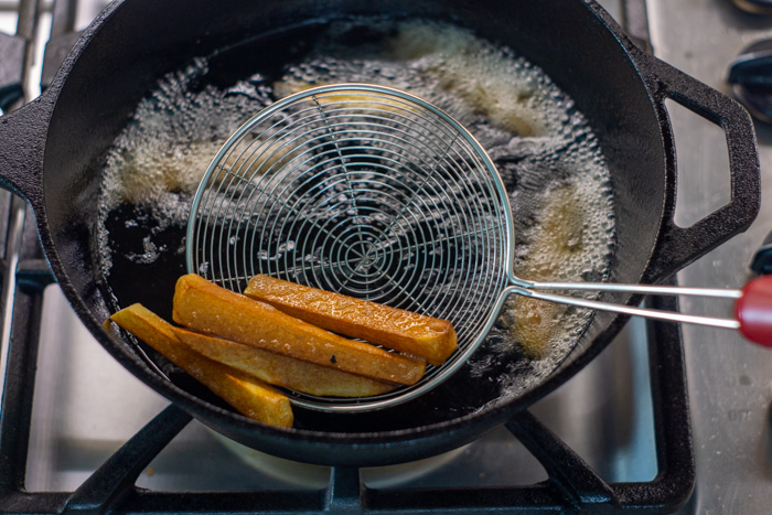 Round wire spoon removing fried potatoes from hot oil in a cast iron skillet on a gas stovetop