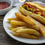 Homemade french fries next to a hot dog on a round white plate with a small round white bowl of ketchup next to a white towel behind the plate all on a wooden surface (with title overlay)