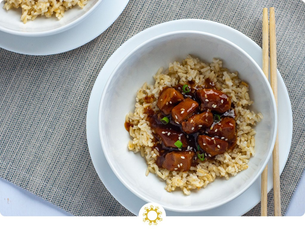 Orange Chicken in the Instant Pot on top of a bed of rice in a round white bowl on a round white plate next to bamboo chopsticks with another serving behind on a grey placemat on a white wooden surface (with logo overlay)