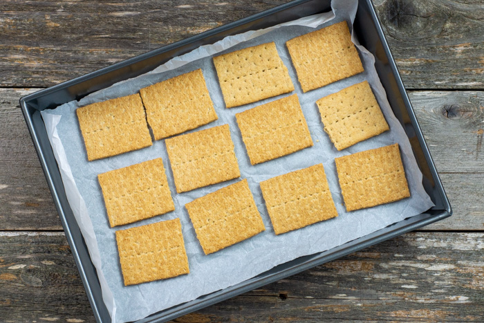 Graham cracker squares on a piece of parchment paper on a baking sheet on a wooden surface