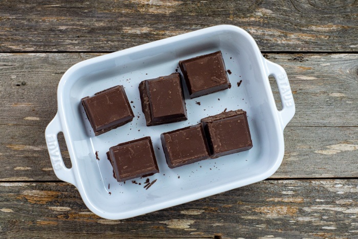 Baking chocolate squares in a white casserole dish on a wooden surface