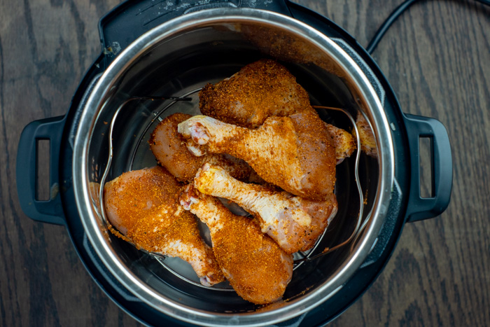 Chicken drumsticks covered with bbq seasoning on the metal tray in an instant pot over a wooden surface