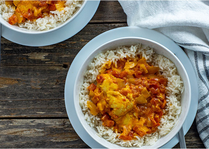 Instant pot butter chicken over white rice in a round white bowl on a round white plate with a stainless steel fork next to a white and gray towel with a second bowl behind all on a wooden surface